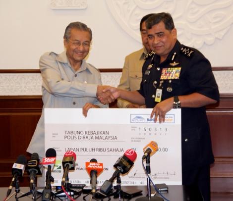Tun Dr Mahathir Mohamad handing over the mock checque to Deputy IGP Tan Sri Khalid Abu Bakar