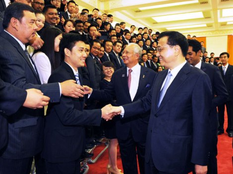 Premier Li Keqiang and Malaysian Prime Minister Najib Razak meet youth representatives of the two countries at the Great Hall of the People in Beijing on Saturday. [Photo/Xinhua]
