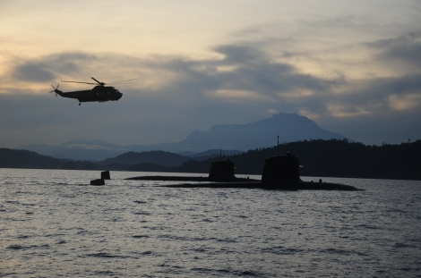 Two RMN Perdana Class submarines in Sepanggar Bay and an RMAF S61 Nuri helicopter approaching and the Mount Kinabalu as the backdrop