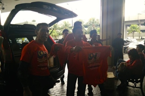 A group seen selling their red t-shirts with the rally logo to members of the public at the entrance of the PWTC building.