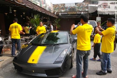 People take photographs of the Lamborghini Gallardo that Jamal says will be included in the lucky draw, in Kuala Lumpur May 25, 2012. — Picture by Jack Ooi